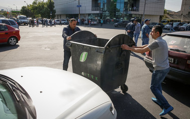 Armenian opposition supporters move a garbage bin to block a road, after protest movement leader Nikol Pashinyan announced a nationwide campaign of civil disobedience in Yerevan