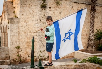 Cute Caucasian boy with a large flag of Israel in his hands.