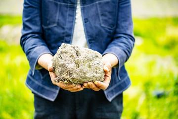 人が畑で大きな土の塊を手で持つ
