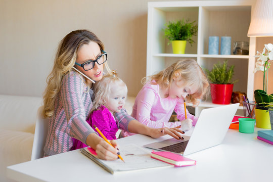 Busy woman trying to work while babysitting two kids