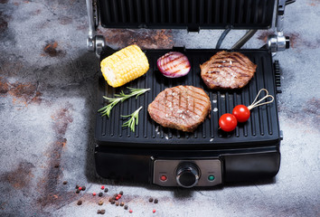 Wall Mural - Preparation of beef steaks and vegetables on an electric grill on a gray concrete background