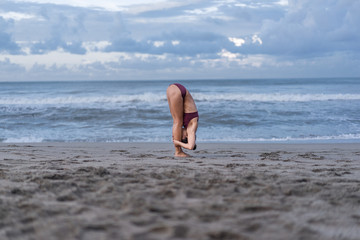 side view of young woman practicing yoga in Standing Forward Bend pose (Uttanasana) on seashore