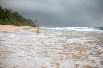 Back view of a attractive woman holding surf board in hands on coastline.