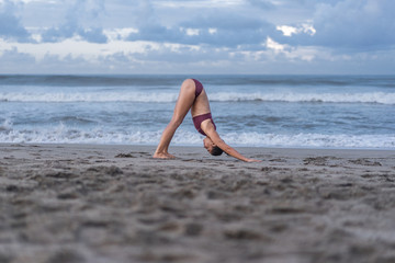 side view of attractive young woman practicing yoga in Downward-Facing Dog pose (Adho Mukha Svanasana) on seashore