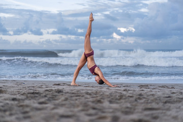 side view of sporty young woman practicing yoga in One Legged Downward-Facing Dog pose (Eka Pada Adho Mukha Svanasana) on seashore