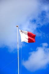 Maltese flag unfurled against a blue sky with fluffy clouds, Malta.