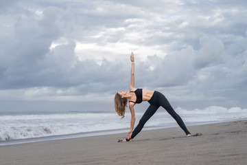 beautiful young woman practicing yoga in Triangle pose (Trikonasana) on seashore
