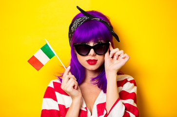 Young surprised girl with purple hair holding Italian flag on yellow background.