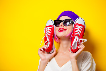 Young girl with pink hair in purple hat and sunglasses holding a red gumshoes on yellow background