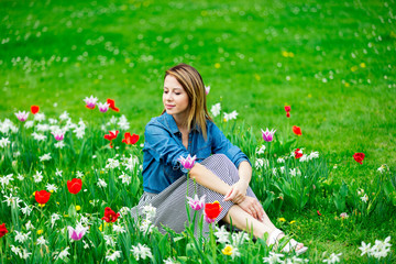 Young redhead girl sitting at tulips meadow in springtime garden