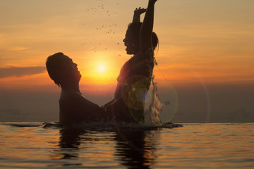 Faith and trust with strong warm feeling and emotional connection.  True love and romance with silhouette and sunset in background.