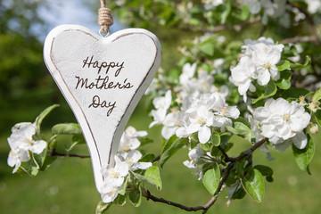 """weißes Herz mit Aufschrift""""Happy Mother's Day"""" vor Apfelblüten"""