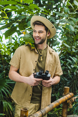 smiling young man with parrot on shoulder and binoculars in jungle