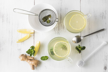 Ginger tea with mint, lemon and honey in a glass cup on a white wooden table, top view