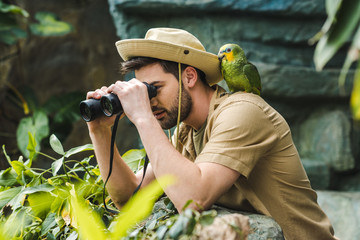 handsome young man with parrot on shoulder looking through binoculars in jungle