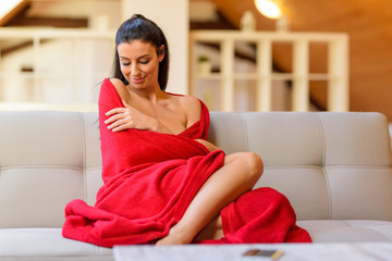 A beautiful woman relaxing on the sofa in a blanket