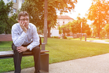 Portrait of a Business man being bored on a bench