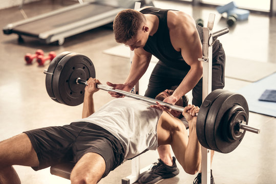 athletic trainer helping sportsman lifting barbell with heavy weight plates in gym