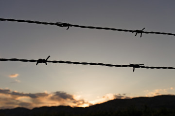 barbed wire fence in front of sunset