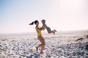 caucasian mother and son having fun at the beach