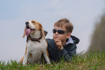 European boy with Beagle dog lying on grass