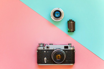 Vintage film photo camera lens film roll and accessories on pink and blue colourful pastel trendy modern fashion pin-up background. Technology development photographer hobby classic memory trip
