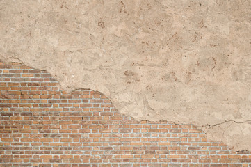 Vintage textured old brick wall with stained and shabby uneven plaster background. Copy space for text.