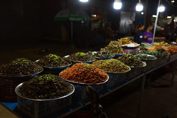Cambodian night street food market with many kinds of insects, spiders and worms for sale