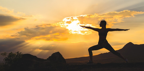 Silhouette of young woman practicing yoga or pilates at sunset or sunrise in beautiful mountain location, doing lunge exercise, standing in Warrior.