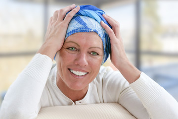 Elegant oncology patient with headscarf sitting on couch, smiling