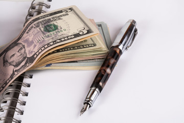 Dollar banknotes and pen, notebook