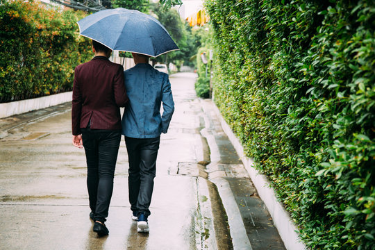 Gay couple holding umbrella and hands together. Back of homosexual men walking in the rain