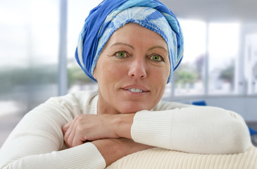 beautiful oncology patient with headscarf sitting on couch, smiling