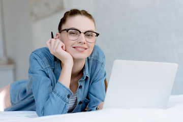 young smiling female freelancer with laptop on bed