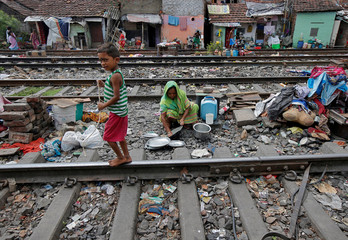 A boy walks past a woman cleaning her kitchen utensils between the railway tracks in a slum area of Kolkata