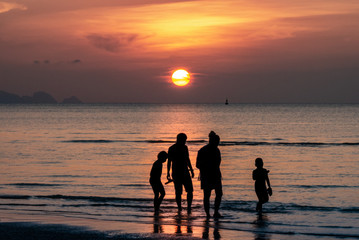 Sonnenuntergang im Meer mit Familie (Silhouette)
