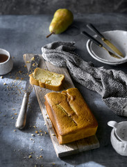 Flay lay of served freshly baked pear cake with tea on rustic table.