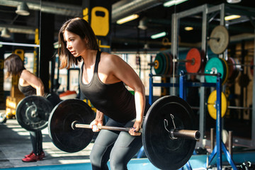 Portrait of strong young woman making deadlift with heavy barbell during workout in modern gym. Healthy lifestyle concept photo
