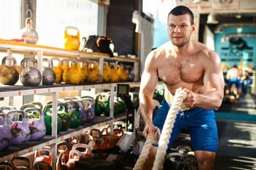 Battle ropes session. Attractive young naked sports man working out in functional training gym doing crossfit exercise with battle ropes copyspace battling ropes cross-fit workout motivation