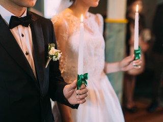 The side view of the newlyweds` hands holding the candles wrapped with green ribbons. Wedding ceremony.