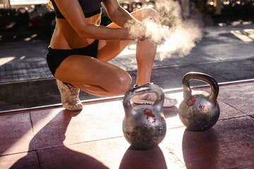 Preparing to training. Hands of woman applying talcum powder before exercize. Fitness background. Copyspace. Two kettlebells at the rubber gym floor