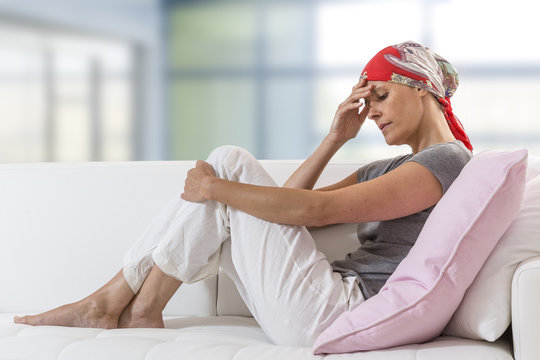 Exhausted woman after chemotherapy resting at home lying on couch