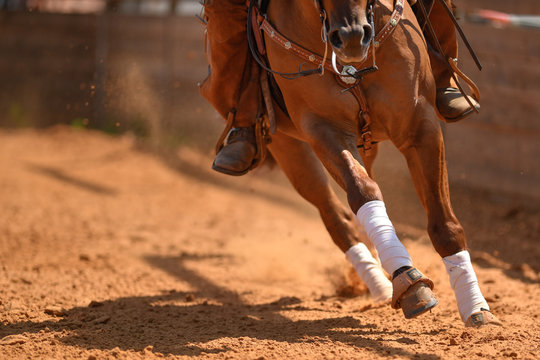 The rider on a reining horse slides to a stop in the red clay an arena.