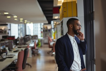 Businessman talking on smartphone while standing in office