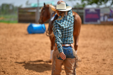 Cowgirl in hat, jeans, cowboy chaps and checkered shirt accompanies her horse in a ranch, on the red clay.