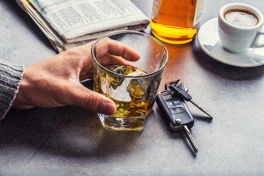Glass of alcohol hand man the keys to the car and irresponsible driver