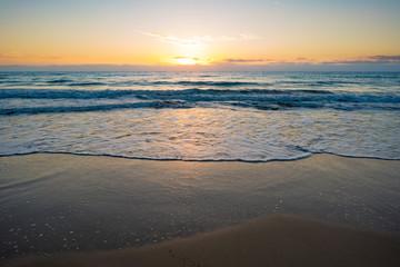 sunset or sunrise on the sea with a sandy beach. Calm sea at dusk