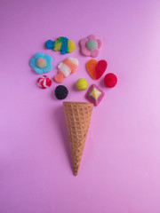 Ice cream cone with jelly candies on pink background