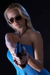 Woman in the blue dress shoots a gun on a black background