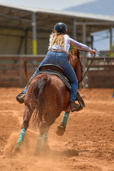 Cowgirl in hat, jeans and white shirt galloping her horse in a ranch, on the red clay.